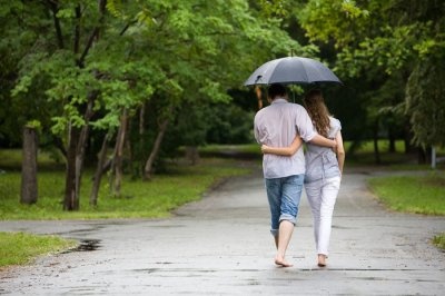 couple walking bare feet in rain under an umbrella