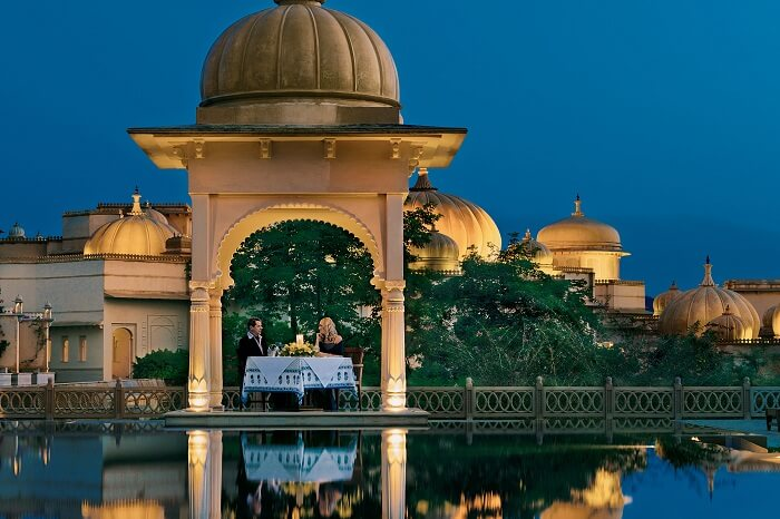 A couple enjoys a private dinner at Oberai Udaivilas in Udaipur that is one of the best honeymoon places in India in October