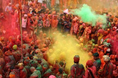 People throw colors to each other during the Holi celebration at Krishna temple