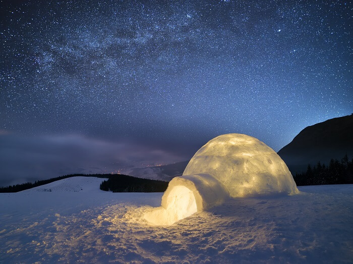 Night landscape with a snow igloo with light