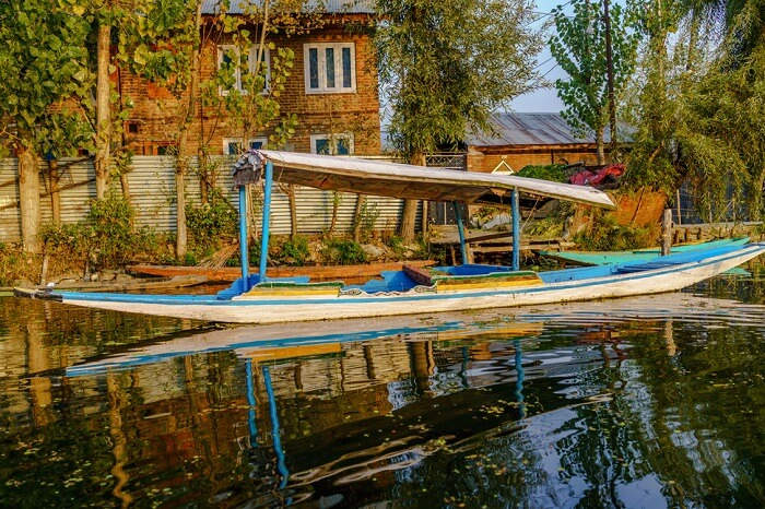 Old rugged wooden boat floated by an old house on a shore of Dal Lake during sunset