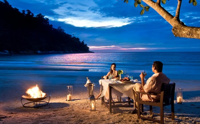 Couple enjoying a surprise and romantic dinner by the beach