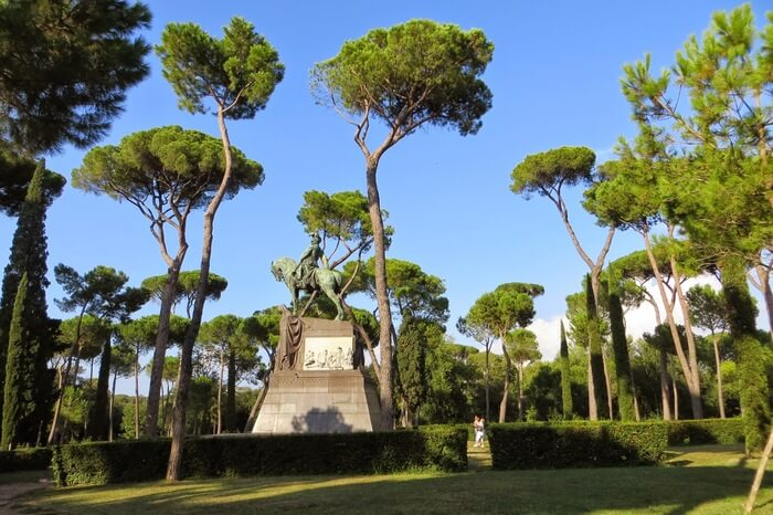 tall trees and a stone statue in a garden