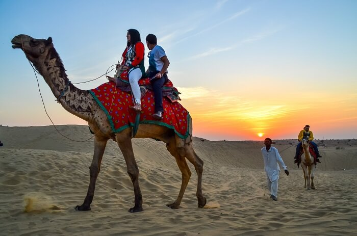 couple enjoying desert camel safari in Jaisalmer, India