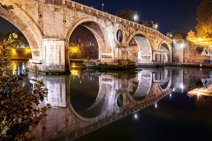 an old bridge reflexion in river water