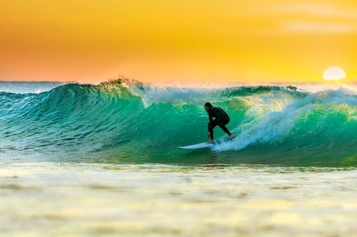 A traveler surfing in Arabian sea near a coast in Kovalam