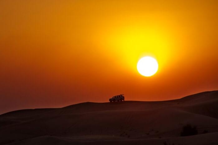Travelers watching sunset during desert safari in Dubai