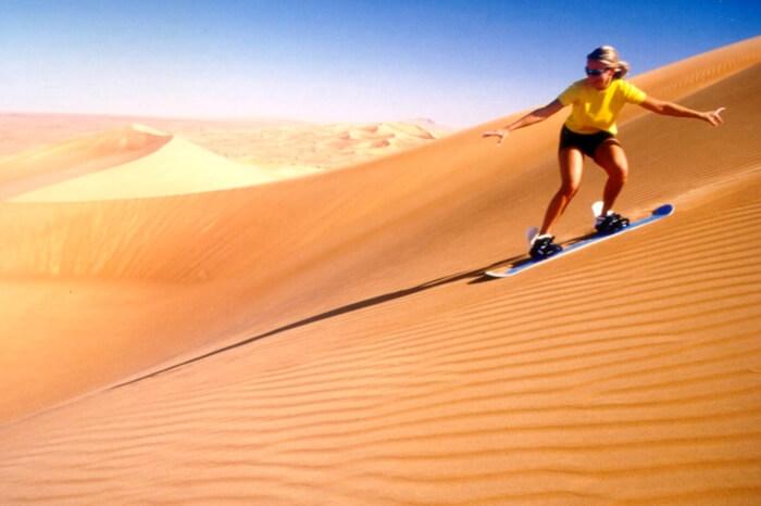 A traveler enjoying sand skiing during desert safari in Dubai