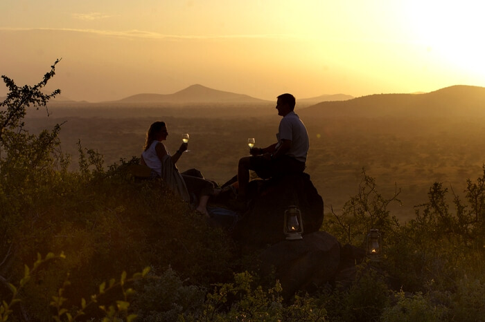 Couple drinking wine during their safari honeymoon in South Africa