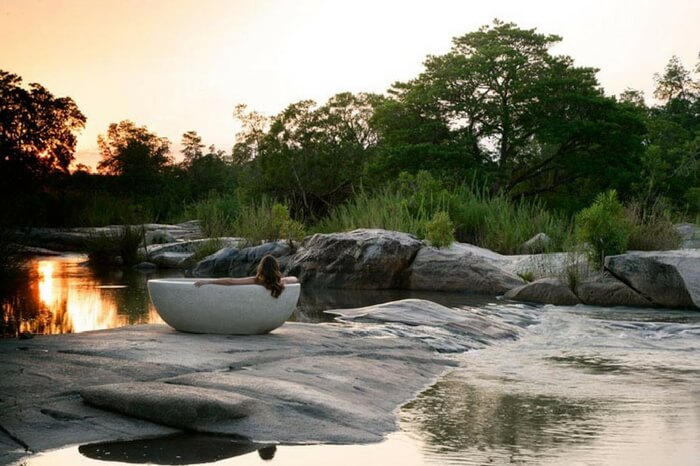 A honeymooner bathing in a tub in a jungle lodge during a safari honeymoon in South Africa