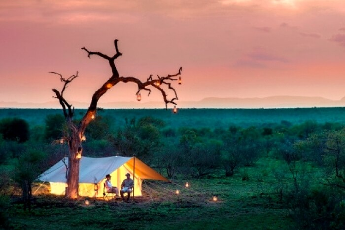 Couple sitting outside a tented lodge in South Africa