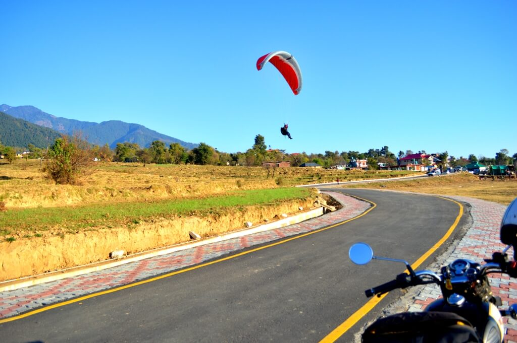 a guy landing on road after paragliding