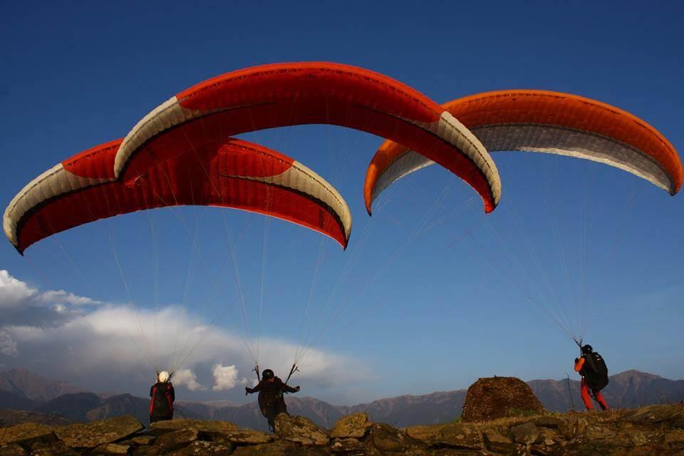 three guys paragliding in Bir Billing