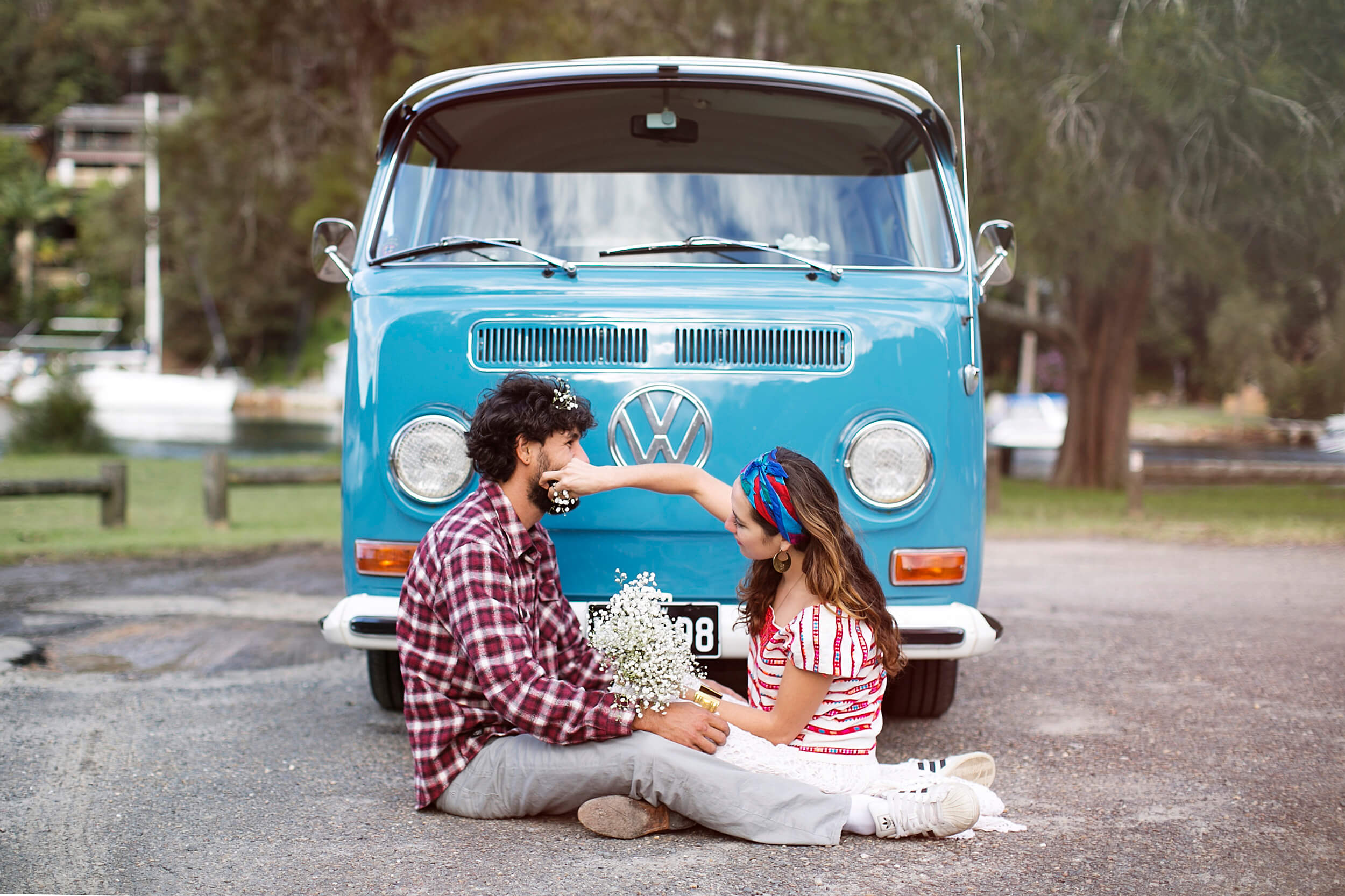 A couple sitting in front of a Kombi van