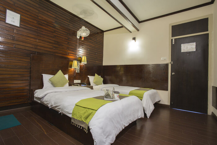 two beds in a wooden floor hotel room