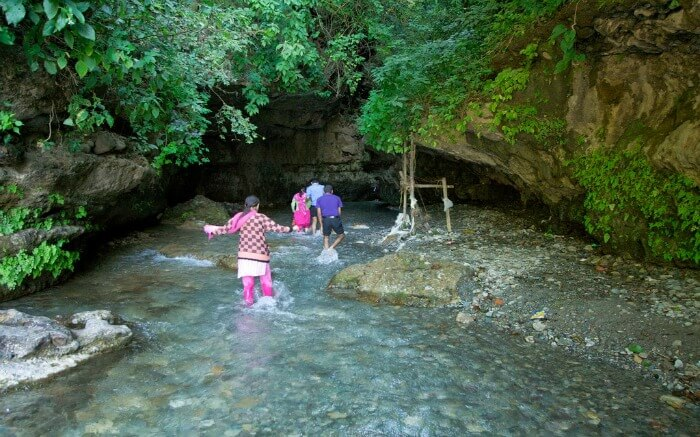 people crossing a stream to go to Robbers cave