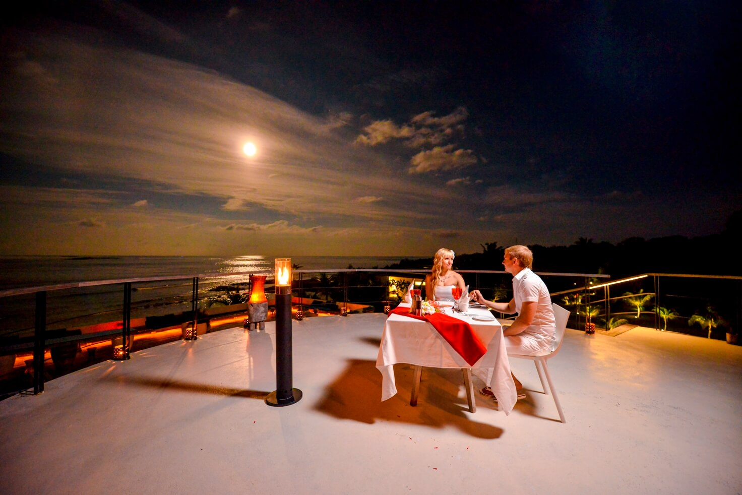 A couple on a cruise having dinner in moonlight
