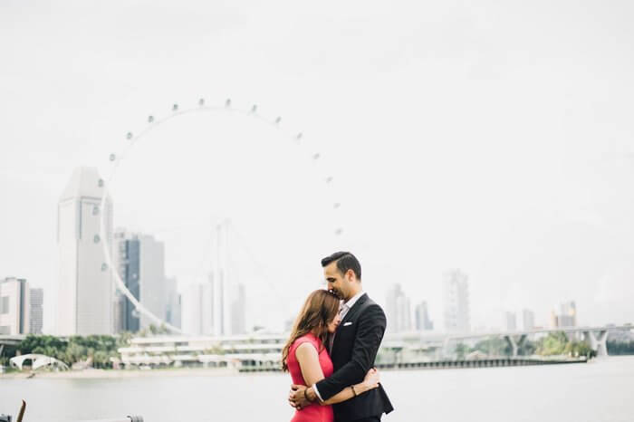 A couple hugging each other in front of Singapore flyer