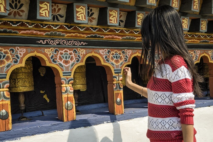solo female traveler exploring a Buddhist temple in Bhutan