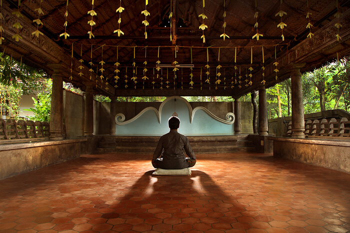 a guy meditating in an ashram