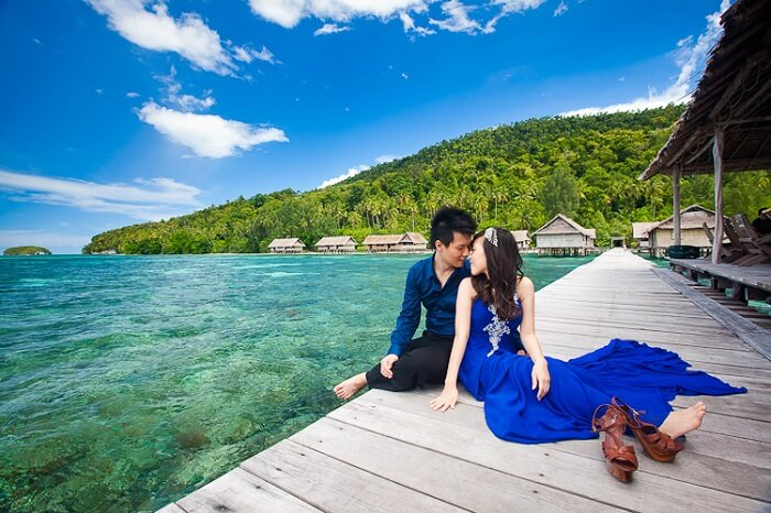 Romantic couple sitting by the beach in Raja Ampat Islands