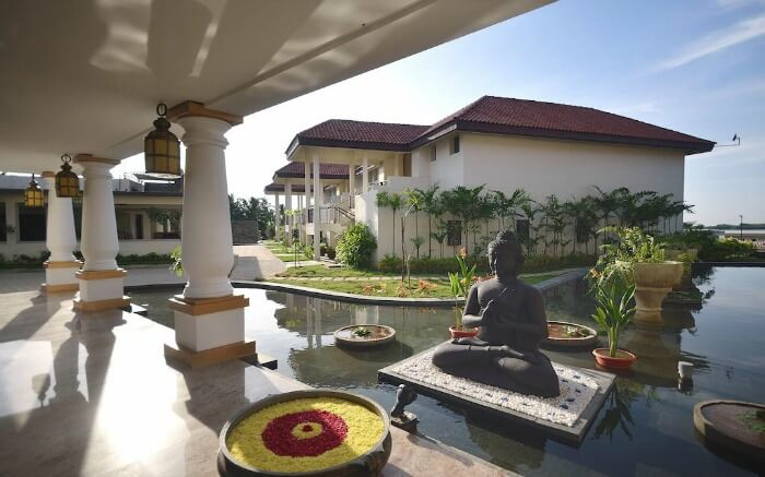 A Buddha statue in Windflower Resort and Spa Pondicherry on a bright day