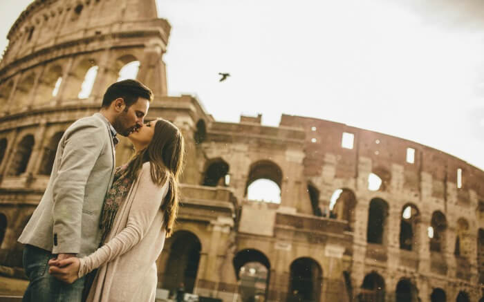 : A couple kissing in front of Colosseum