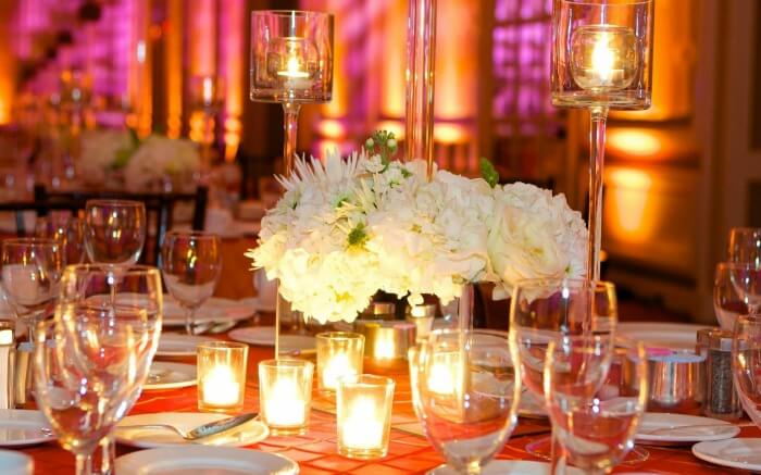 Floral and candle light decoration on a table with glasses