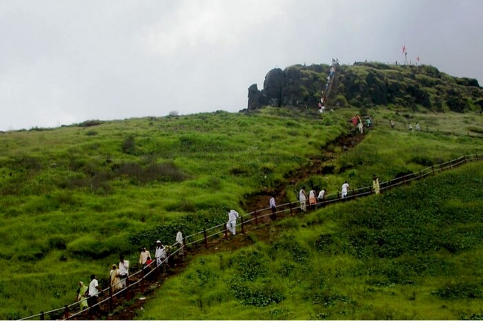 Tourists trekking to the top of Kalsubai in Maharashtra during monsoon