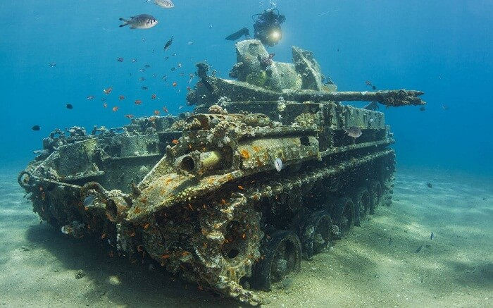 Sea divers passing a tank that got sunk in the Gulf of Aqaba in Jordan