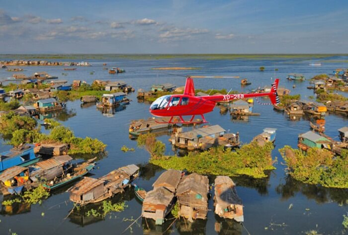 A helicopter flying over the floating villages of Tonle Sap Lake in Siem Reap