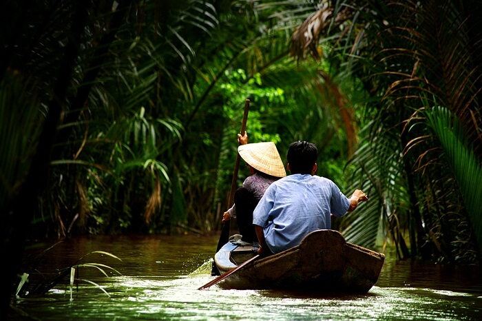 Vietnamese people paddling in the Mekong delta in Ho Chi Minh city