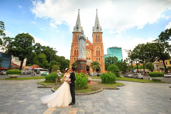 A newlywed couple taking pictures outside the Notre Dame Cathedral in Ho Chi Minh city in Vietnam