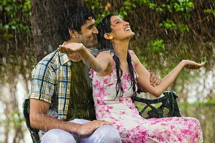 couple sitting under tree mumbai rain
