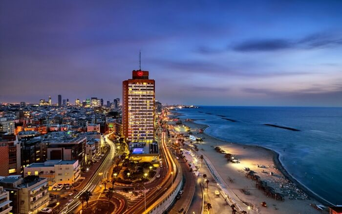 A well lit tel Aviv city by the Mediterranean at sunset in Israel