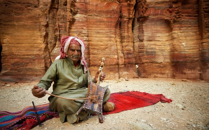 An old bedouin man playing traditional instrument