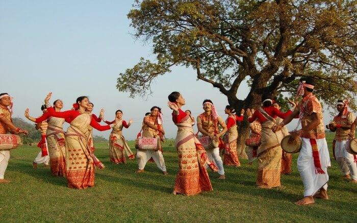 Assamese women and men dancing during Bihu