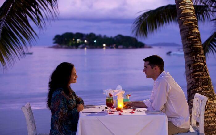 Couple dining by the beach during their safari honeymoon in Tanzania