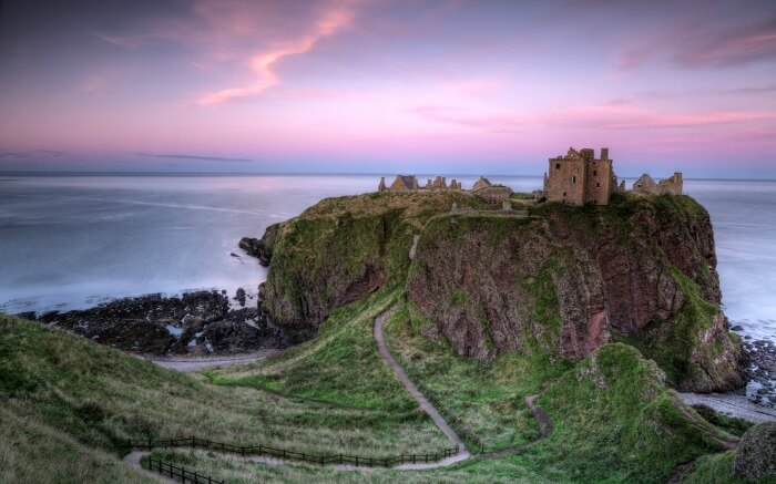Dunnottar Castle with pink tinged sky in backdrop