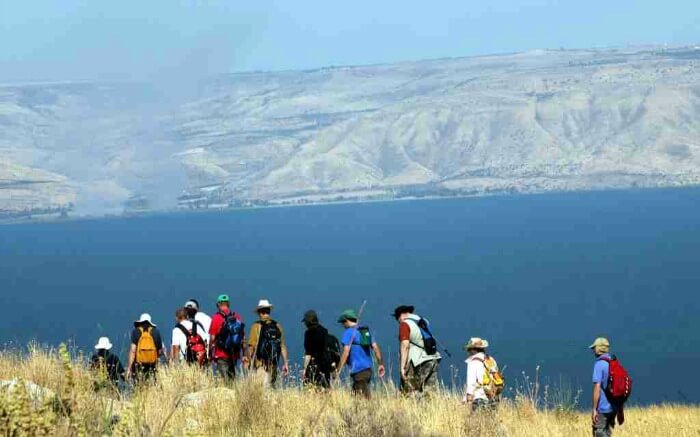 Hikers walking past Sea of Galilee in Israel
