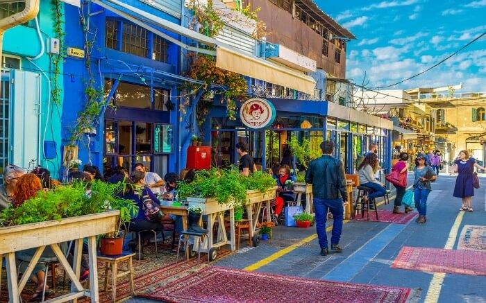 Israelis sitting in a roadside cafe in Flea market in Israel