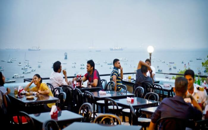 People having food at the rooftop dining space of Bayview cafe in Mumbai