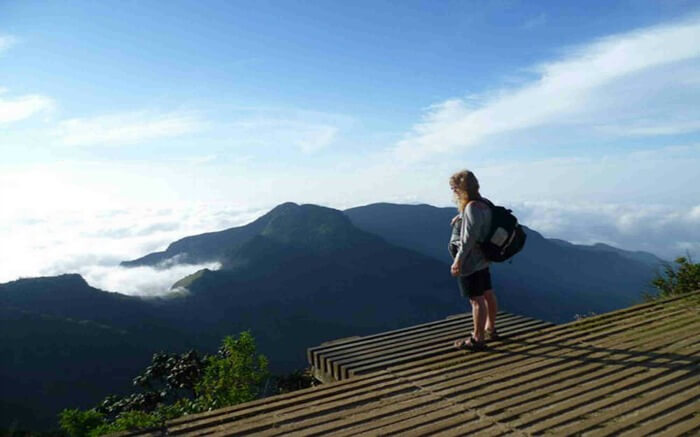 Traveler standing on a raised platform overlooking Horton Plains National Park in Kandy