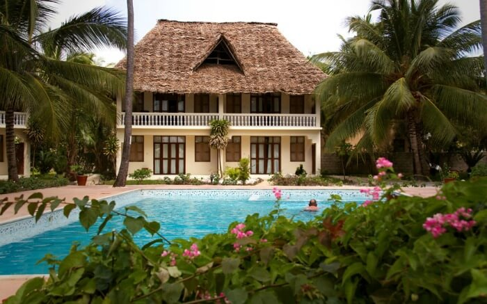a Zanzibari thatched roof villa with a pool