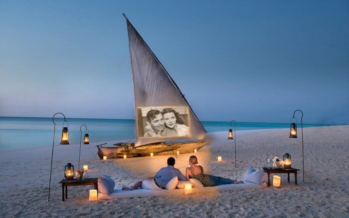 a couple sitting on white sand beach watching an old movie