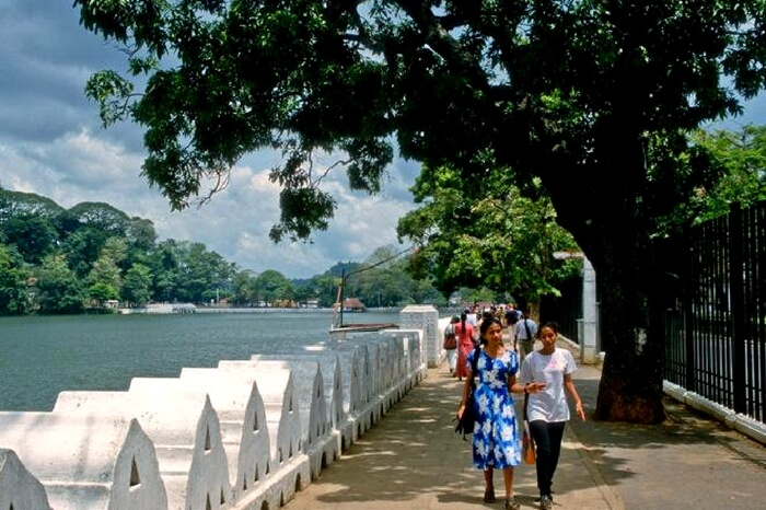Tourists taking a leisure walk by the Kandy Lake in Sri Lanka