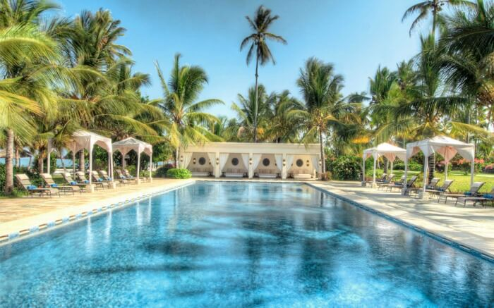 an open pool in a resort with palm trees around it