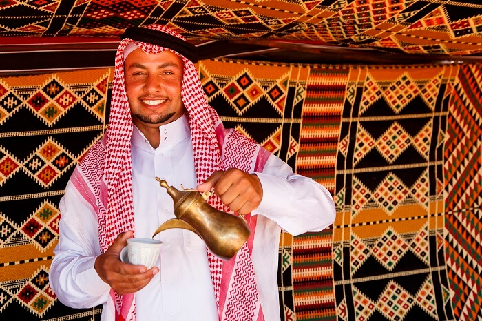 A friendly and welcoming Jordanian happily serving tea to the tourists