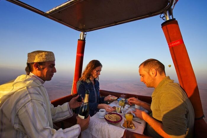 A couple dining in a hot air balloon flying over the Sahara Desert in Morocco