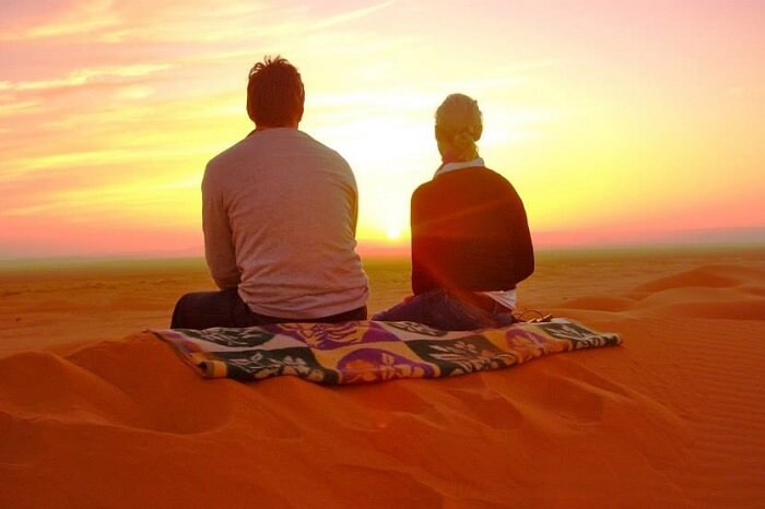 A couple enjoying a beautiful sunset in the Sahara Desert on their Morocco honeymoon